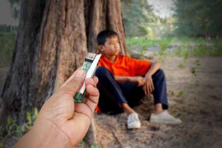 misuse: Hand give cigarette to sad boy,the concept of drug problems in youth.
