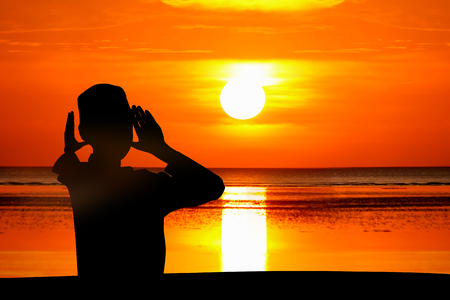 The boy praying at sunset on the beach. Stock Photo