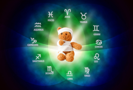 seer: The teddy bear with bandage ,sign of misfortune on blue background of the horoscope and health concept.