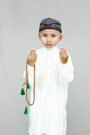 all weather: Muslim little cute kid with hat and pray on gray background.