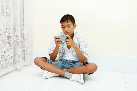 portrait of young boy with mobile phone in home ,his look like serious and strain. Stock Photo