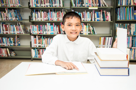 asian boy doing homework at the library. Stock Photo