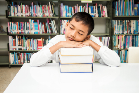 Asian boy sleeping with his homework at the library.