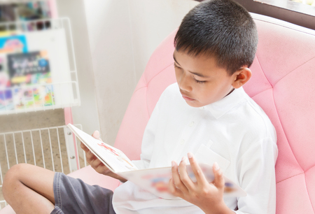 The boy is reading a book on a pink sofa.