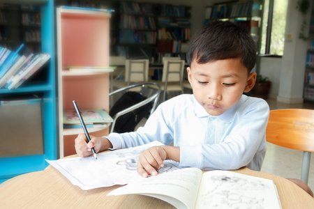 A little boy is drawing cartoon in his home.
