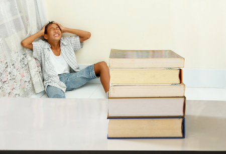 Many Textbook on the table with teenage boy who has stress.