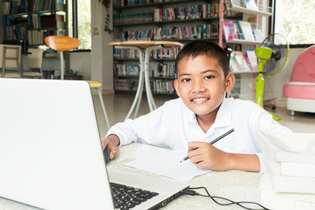 Boy research computer To do homework at the library