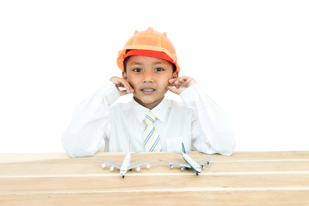 Asian boy in uniform of engineer and toy plane.
