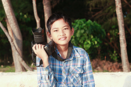 little boy with checkered shirt holding a camera and smiling isolated on nature background 版權商用圖片