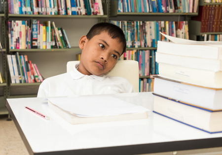 boy is tired and boring his  homework.