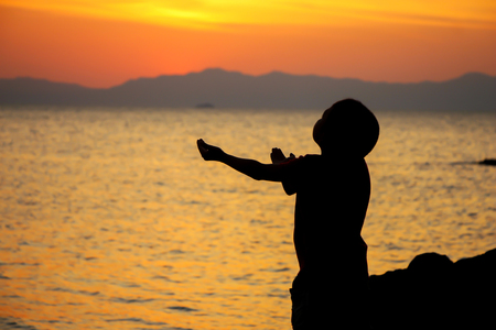 The boy praying at sunset on the beach. Imagens