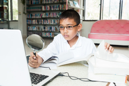 Asian boy who was wearing eyeglasses research computer To do homework at the library, 版權商用圖片
