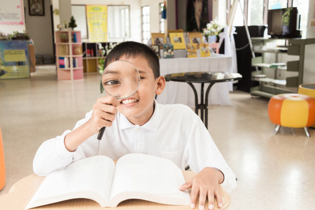 Asian boy with magnifier he searching a map for doing his homework at the library. 版權商用圖片
