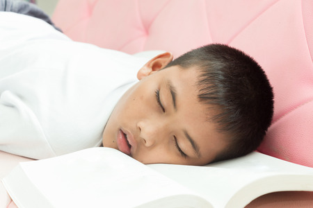 Asian boy sleeping with his homework at the pink sofa. Stock Photo