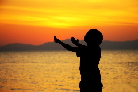 silhouette boy praying to god on the beach at sunset.