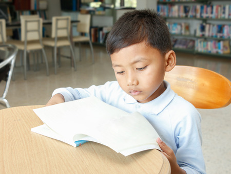 asian boy reading a book at the library.