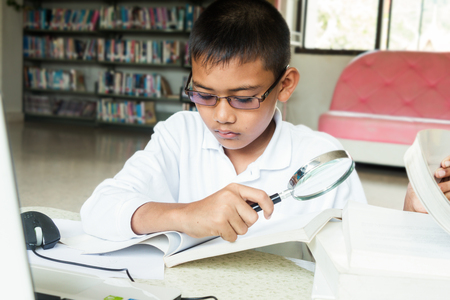 Asian boy who was wearing eyeglasses research computer To do homework at the library, Stock Photo