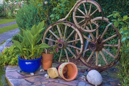 flowerbed: Designed wheel dekoration on the flowerbed with flowers Stock Photo