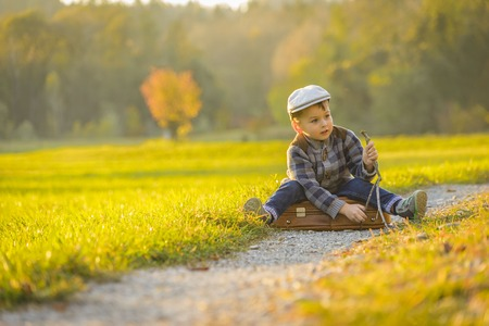 Happy little boy playing on road at sunset. He standing in the field and holding in hands suitcase and balloons. Stock fotó