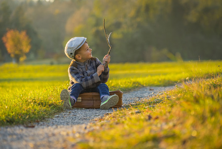 Happy little boy playing on road at sunset. He standing in the field and holding in hands suitcase and balloons. 写真素材