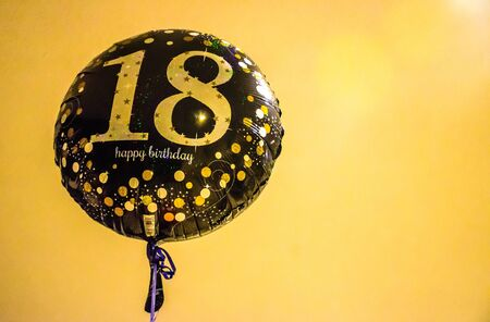 Balloon with number '18' in golden fonts and happy birthday's wishes in yellow background Archivio Fotografico
