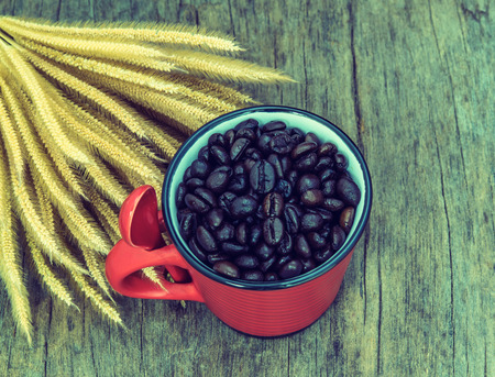 Vintage roasted coffee beans in red cup on the old background photo