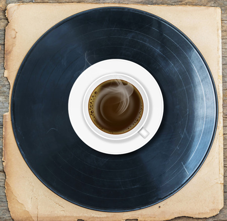 Coffee with old gramophone on old paper and wood.