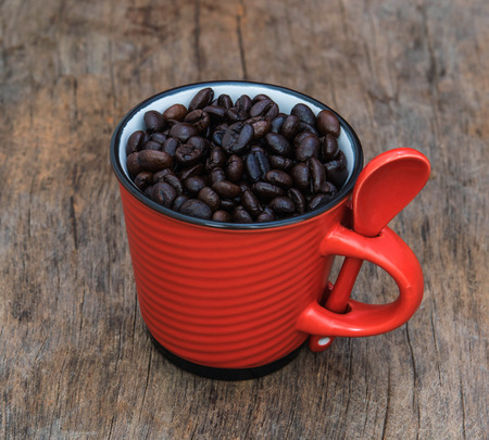 roasted coffee beans in red cup on the old background photo