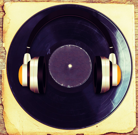 Vintage headphones  with gramophone on old paper and wood. Фото со стока