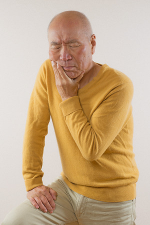 Japanese wincing in pain in seniors Stock Photo