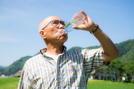Mientras camina en el país abastecimiento de agua viva a japoneses mayores