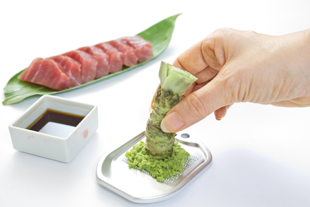 Sashimi and raw with wasabi and female hands