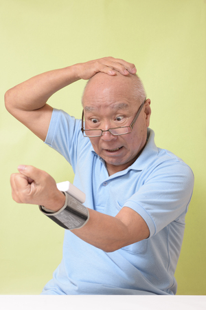 Senior has a blood pressure measurement Stock Photo