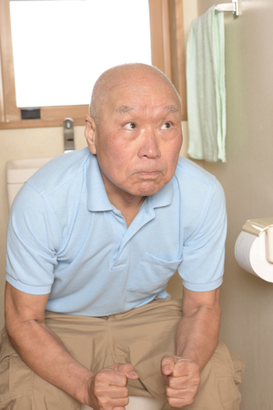 Seniors suffer from constipation on the toilet 스톡 콘텐츠