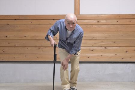 An old man carrying a walking stick, walking 版權商用圖片