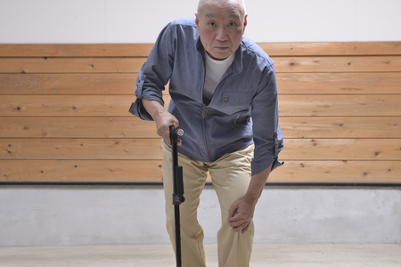 An old man carrying a walking stick, walking 스톡 콘텐츠