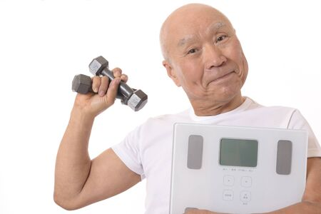 Senior with scale and dumbbell Stok Fotoğraf