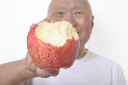 Senior eating apples with a smile
