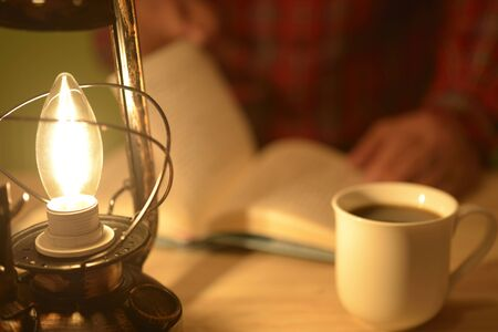 a man reading a book with a lantern light Stock fotó