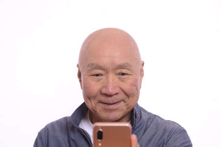 Japanese senior man operates smartphone with a smile
