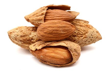 almonds in their skins and peeled with leaf isolated on white background.