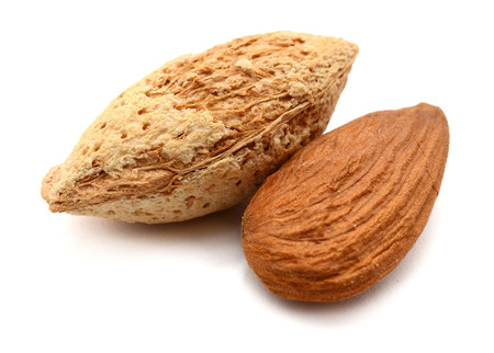 heap of almonds in his skins and peeled with leaf isolated on white background.