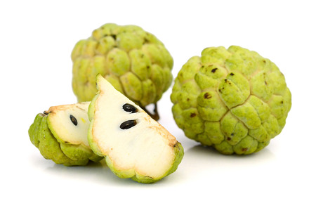 whole and half cut ripe custard apple (red skin) on white background