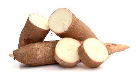 Corte y mandioca entera (yuca) aislado sobre fondo blanco.