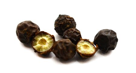 Heap of raw, natural, unprocessed black pepper peppercorns over white background