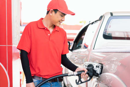 Asian gas station worker man filling high energy power fuel in auto car tank in petrol station, commercial service for benzine, diesel, gasohol, gasoline.