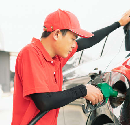 Asian gas station worker man holding green fuel nozzle into one hand and filling high energy power fuel into black auto car tank in petrol station, commercial service for benzine, diesel, gasohol, gasoline. Reklamní fotografie