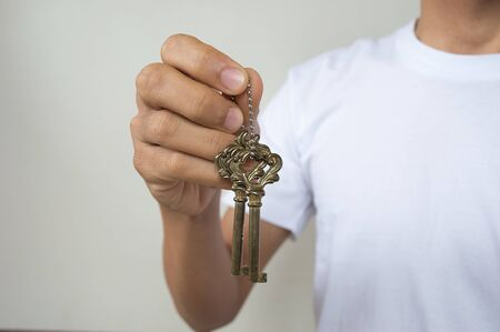 key chain: Gold key chain with key in hand a man Stock Photo