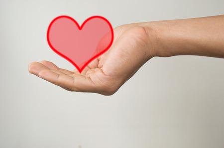 men hand holding heart isolated on gray photo