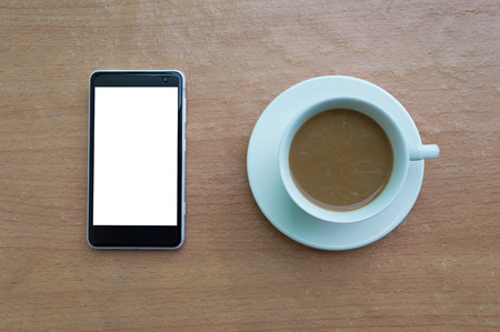 Smartphone and coffee cup on wooden desk